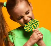 Happy young little child girl kid bite sweet lollypop candy. On yellow background Stock Photos