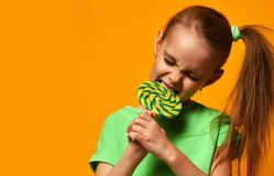 Happy young little child girl kid bite sweet lollypop candy. On yellow background Stock Photography