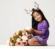Happy young little child girl kid with bouquet of flowers and deer rim Stock Photography