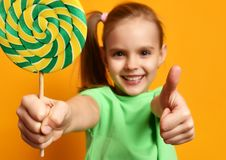Happy young little child girl with sweet lollypop candy surprised screaming yelling. Happy young little child girl with sweet lollypop candy show thumbs up Stock Image