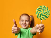 Happy young little child girl with sweet lollypop candy surprised screaming yelling. Happy young little child girl with sweet lollypop candy show thumbs up Stock Photo