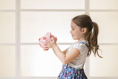 Happy young little girl with piggy bank. Portrait of happy young little girl looking at her pink piggy bank. Education, school and money saving concept. Junior Stock Image