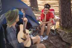 Happy young looking at her boyfriend playing guitar by tent Royalty Free Stock Images