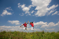 Happy Young love Couple - jumping under blue sky Stock Photo