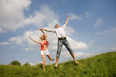 Happy Young love Couple - jumping under blue sky Stock Photos