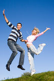 Happy Young love Couple - jumping under blue sky Royalty Free Stock Photo
