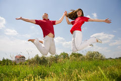 Happy Young Love Couple - Jumping Under Blue Sky Stock Image