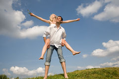 Happy Young love Couple - jumping under sky. Happy Young love Couple - jumping under blue sky Royalty Free Stock Image