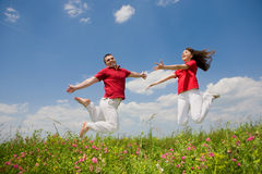 Happy Young love Couple - jumping under sky Royalty Free Stock Images