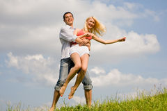 Happy Young love Couple - jumping under sky Royalty Free Stock Photography