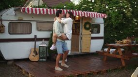 Happy young lovely couple having fun near trailer in the park, girl jumping on man`s arms, he`s whirling her around
