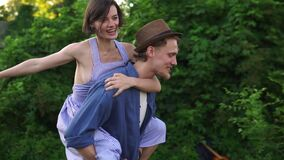 Happy young lovely couple having fun near trailer in the park, man piggybacking girl, running happily, guy whirling her