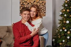 Happy young lovely couple on living room sitting on the couch near christmass tree. Enjoying each other stock images