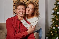 Happy young lovely couple on living room sitting on the couch near christmass tree. Enjoying each other stock photos