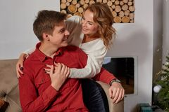 Happy young lovely couple on living room sitting on the couch near christmass tree. Enjoying each other royalty free stock images