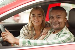 Happy couple buying new car together at the dealership stock photography