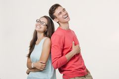 Happy young lovely couple standing back to back and laughing over white background. Friendship and relationships stock photo