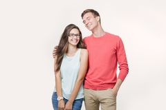 Happy young lovely couple standing together and laughing. Studio shot over white background. Friendship, love and stock photos