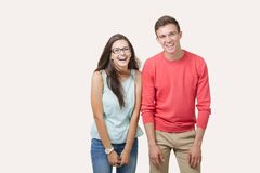 Happy young lovely couple standing together and laughing. Studio shot over white background. Friendship, love and stock images
