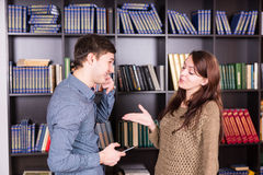 Happy Young Lovers Discussing Inside the Library Royalty Free Stock Images