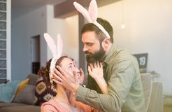 Happy young loving couple bonding to each other with pink rabbit ears on head. Funny family preparing for Easter. Happy young loving couple bonding to each stock image