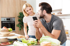 Happy young loving couple cooking together using phone Stock Photo