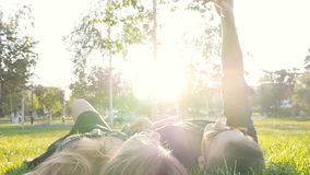 Happy young loving couple making selfie with smart phone while lying on the grass stock video footage