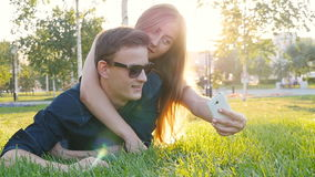 Happy young loving couple making selfie with smart phone while lying on the grass stock video