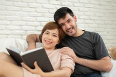 Happy young loving couple reading a book. stock image