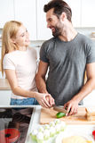 Happy young loving couple standing at kitchen and cooking Stock Photos