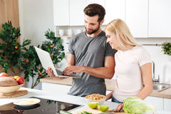Happy young loving couple standing at kitchen and cooking Royalty Free Stock Photos
