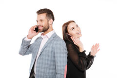 Happy young loving couple talking by phones. Picture of happy young loving couple standing isolated over white background. Looking aside talking by phones Stock Image