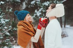 happy young loving couple walking in snowy winter forest, covered with snow and hug stock photo
