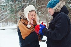 Happy young loving couple walking in snowy winter forest, having fun and kisses Royalty Free Stock Photo