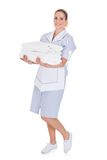 Happy young maid holding towels Stock Photo