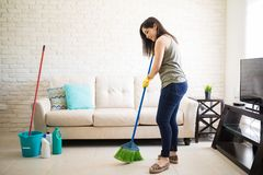 Woman sweeping floor feeling happy. Happy young maid sweeping floor with green and blue broom at home Royalty Free Stock Photos