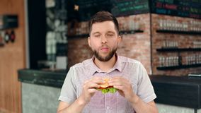 Happy young male biting juicy burger enjoying amazing tasty having positive emotion. Medium shot. Portrait of smiling handsome hungry man eating fresh sandwich stock video