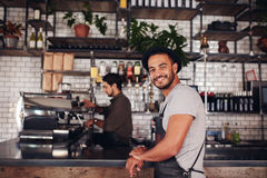 Happy young male coffee shop owner standing Royalty Free Stock Images