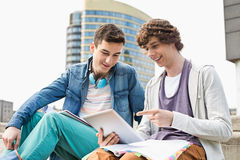 Happy young male college students using digital tablet against building Stock Photos