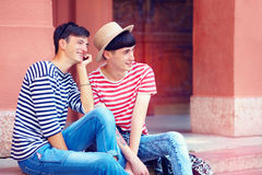 Happy young male couple sitting on stairs Stock Photo