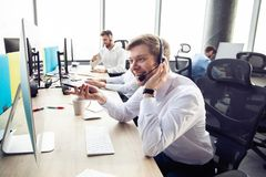 Happy young male customer support executive working in office. royalty free stock photo