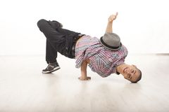 Happy young male dancer sitting on his head  smiling. Young man wearing casual shirt dancing sitting on one hand and his head, performing breakdance moves on Stock Photos