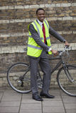 Happy young male engineer with bicycle against brick wall Royalty Free Stock Photography