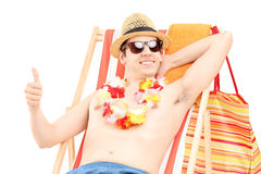 Happy young male enjoying on a beach chair and giving thumb up Royalty Free Stock Photography