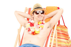 Happy young male enjoying on a beach chair Royalty Free Stock Photos