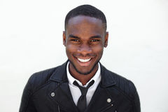 Happy young male fashion model in leather jacket and tie Stock Photos
