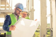 Happy young male and female architects or business partners looking at floor plans on a construction site royalty free stock photos