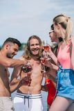 happy young male and female friends holding glases and pouring wine stock image