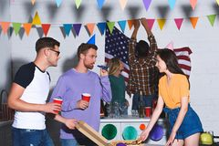 Happy young male and female friends smiling each other while having fun. And partying together stock photos