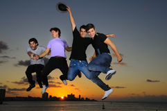 Happy young male group jumping of joy Stock Photos